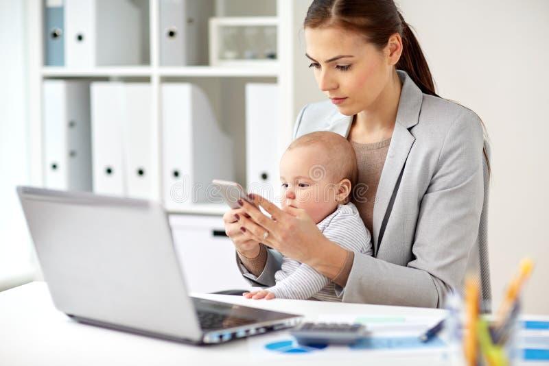 Femme d'affaires avec le bébé et smartphone au bureau photo libre de droits