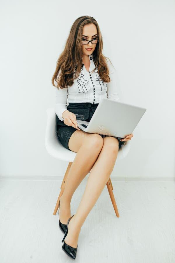 Femme d'affaires avec le carnet dans le bureau se reposant sur la chaise images libres de droits