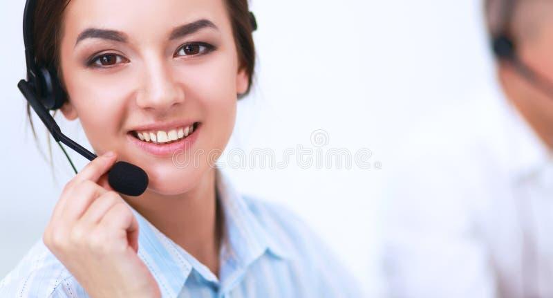 Femme d'affaires avec le casque souriant à l'appareil-photo au centre d'appels photographie stock