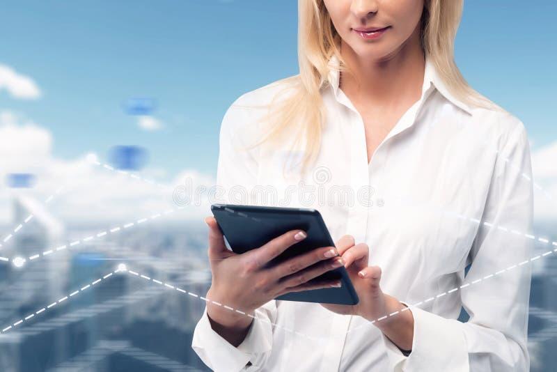 Femme d'affaires avec le comprimé au-dessus de la ville, graphiques photos stock