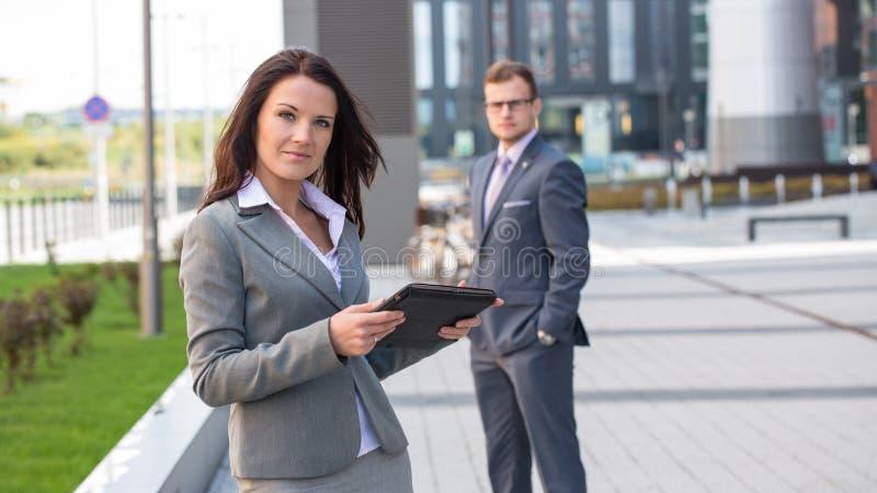 Femme d'affaires avec le comprimé. Dans l'homme d'affaires de fond. photos stock