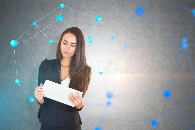 Femme d'affaires avec le comprimé, réseau, mur en béton photos stock