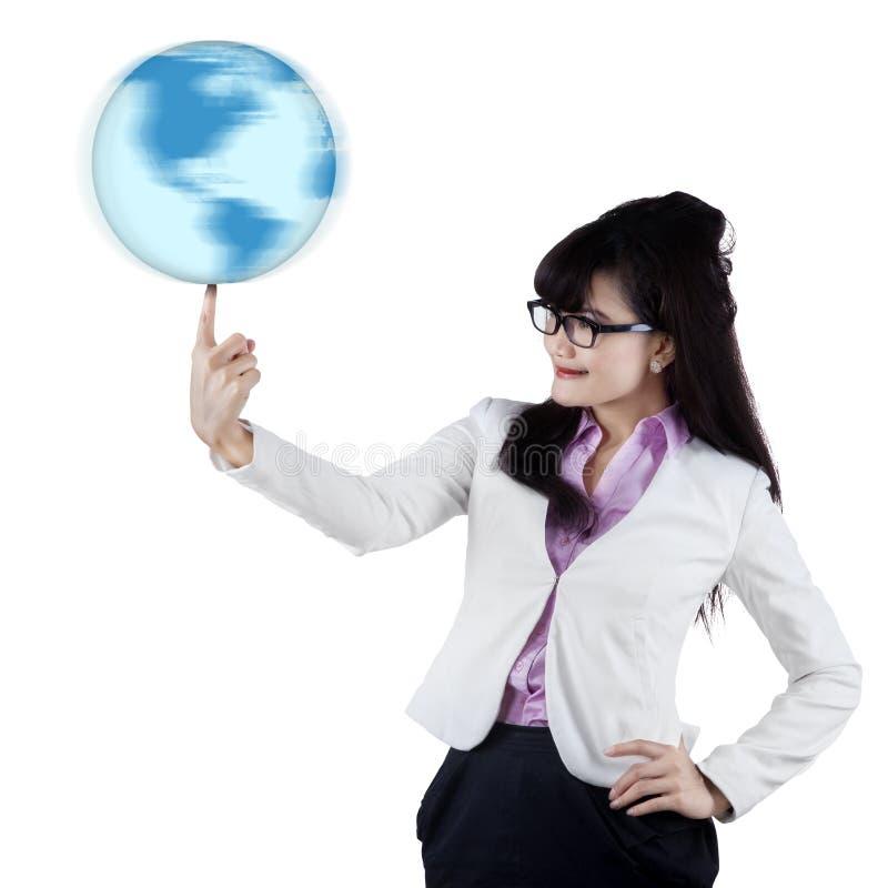 Femme d'affaires avec le globe sur le doigt image stock