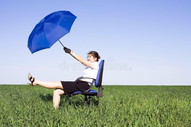 Femme d'affaires avec le parapluie bleu sur le pré images stock