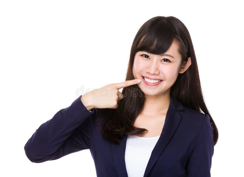 Femme d'affaires avec le point de doigt à ses dents photo stock