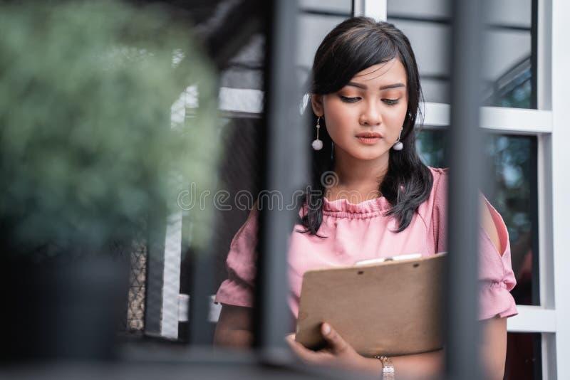 Femme d'affaires avec le presse-papiers vérifiant une certaine substance photos stock