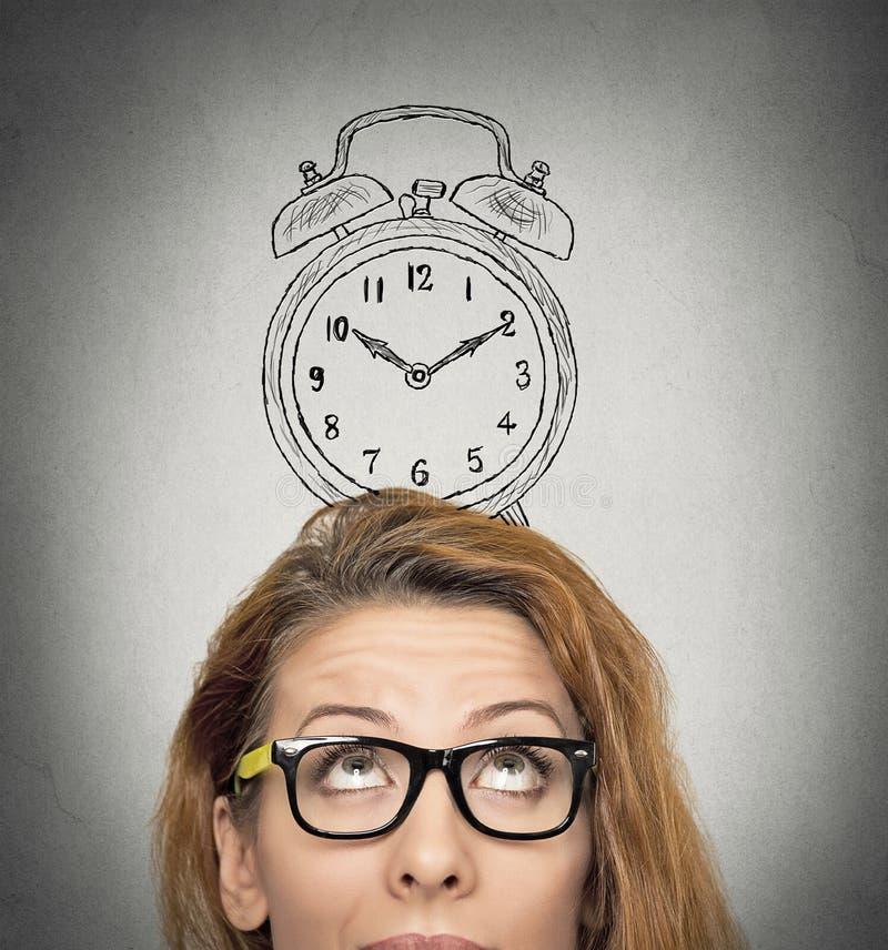 Femme d'affaires avec le réveil au-dessus de sa tête photographie stock libre de droits