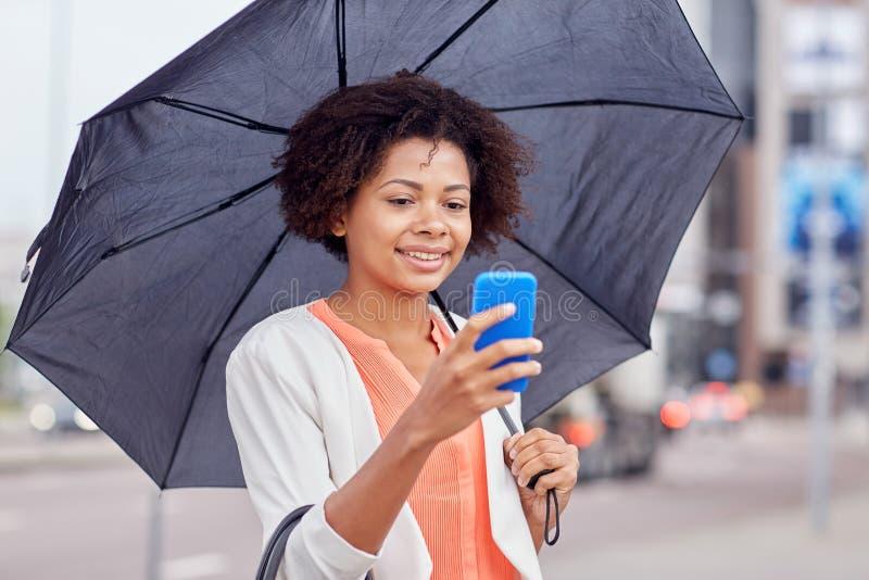 Femme d'affaires avec le service de mini-messages de parapluie sur le smartphone photographie stock libre de droits