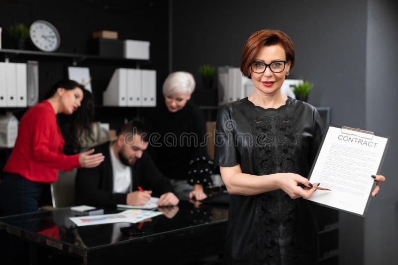 Femme d'affaires avec le stylo et contrat sur le fond des employés de bureau discuter le projet photos stock