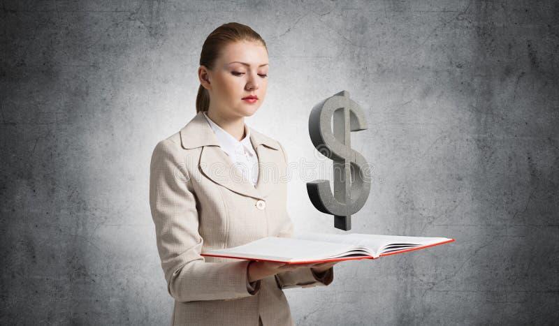 Femme d'affaires avec le symbole dollar au-dessus du livre ouvert photo libre de droits