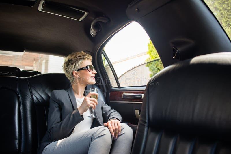 Femme d'affaires avec le verre de champagne dans la limousine photo libre de droits