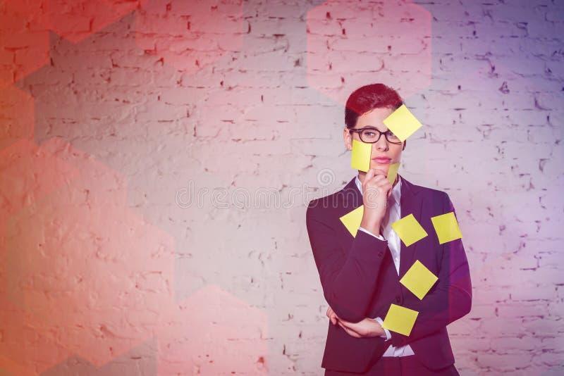 Femme d'affaires avec les notes adhésives jaunes de blanc sur le visage et le costume contre le mur au bureau photographie stock