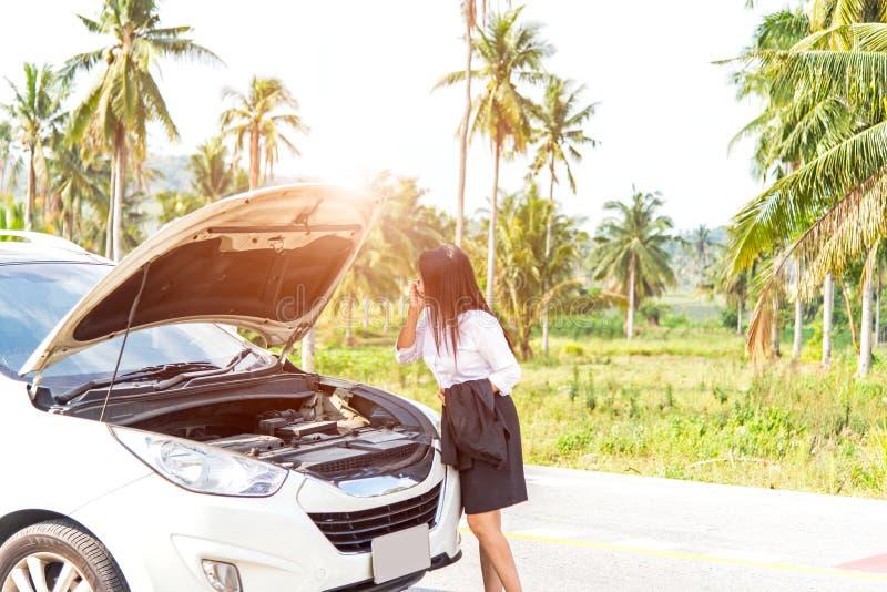 Femme d'affaires avec une voiture cassée réclamant l'aide, photo stock