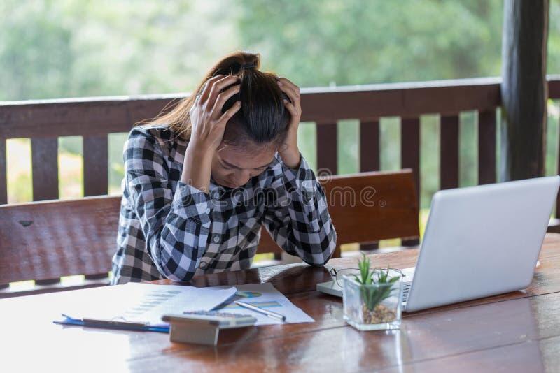 Femme d'affaires ayant le mal de tête tout en travaillant utilisant l'ordinateur portable Comput photos stock