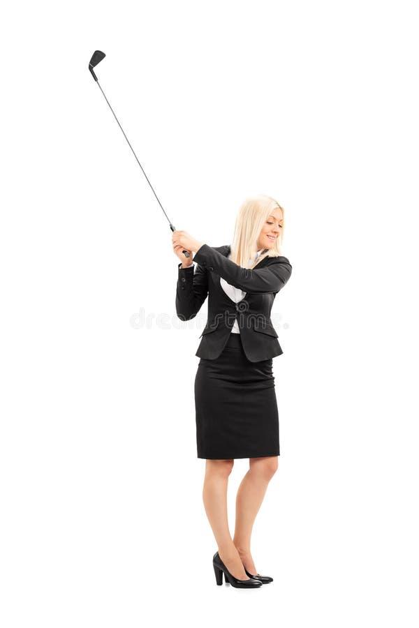 Femme d'affaires balançant un club de golf images libres de droits