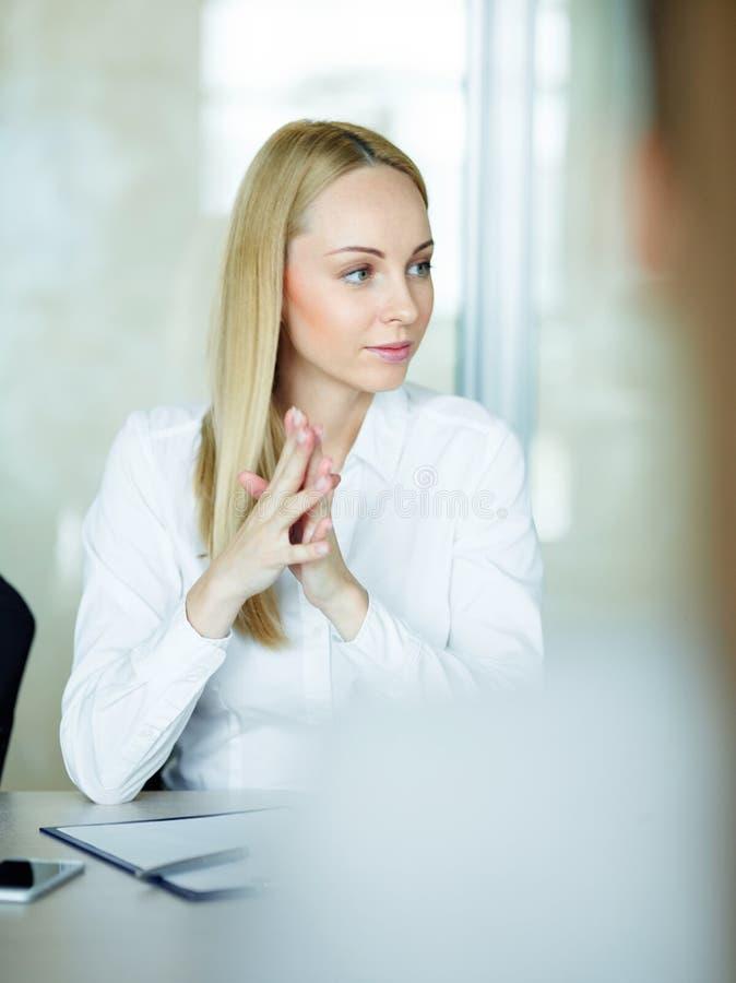 Femme d'affaires blonde Listening lors de la réunion photographie stock