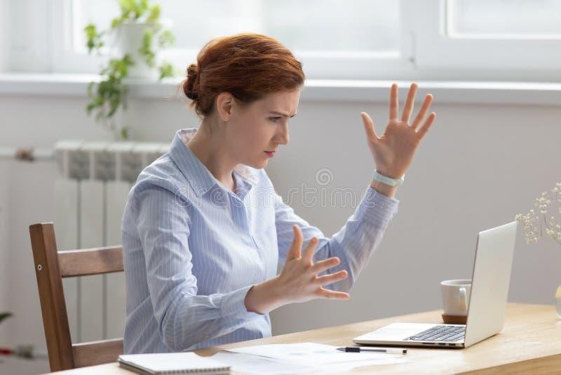Femme d'affaires boulevers?e f?ch?e regardant l'?cran d'ordinateur portable faisant des gestes avec l'irritation photos libres de droits