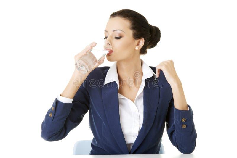 Femme d'affaires buvant l'eau minérale image stock