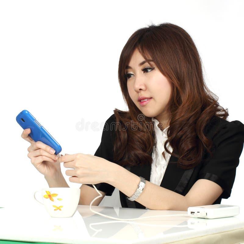 Femme d'affaires chargeant son téléphone portable image libre de droits
