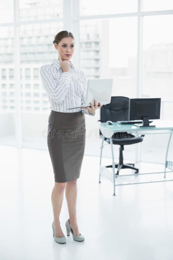 Femme d'affaires chic réfléchie tenant son carnet images stock