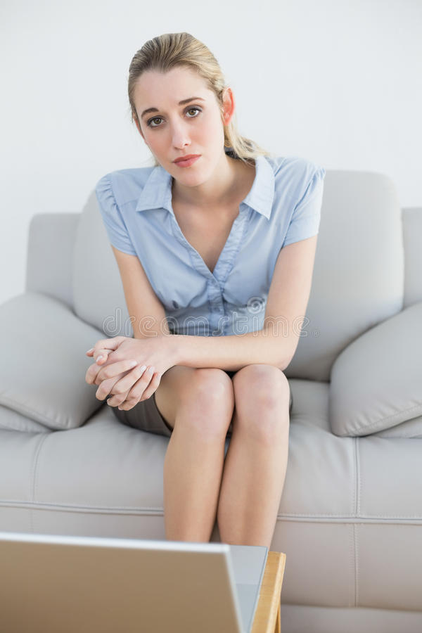Femme d'affaires chic sérieuse s'asseyant sur le divan devant son ordinateur portable image libre de droits