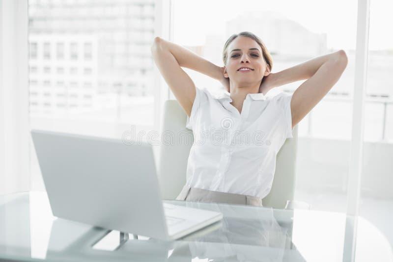 Femme d'affaires chique de détente s'asseyant sur sa chaise pivotante images libres de droits