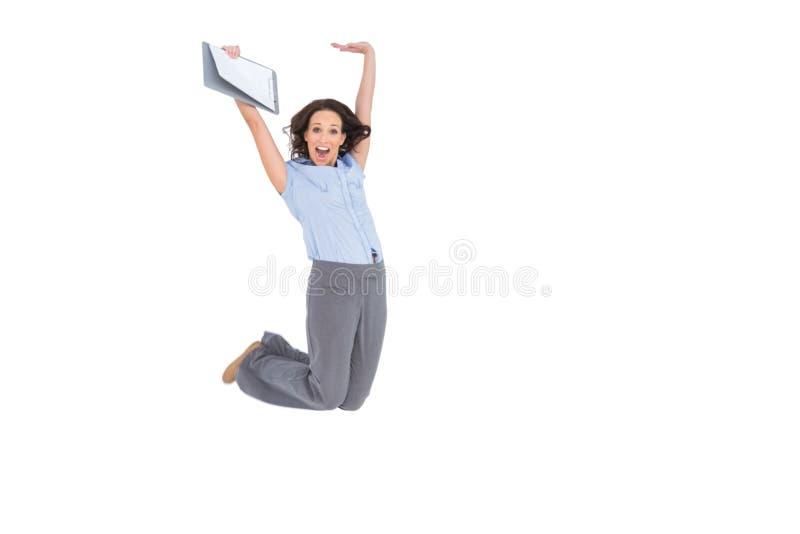 Femme d'affaires chique heureuse sautant tout en tenant le presse-papiers photographie stock libre de droits