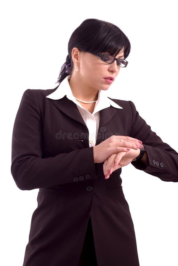 Femme d'affaires contrôlant sa montre photographie stock