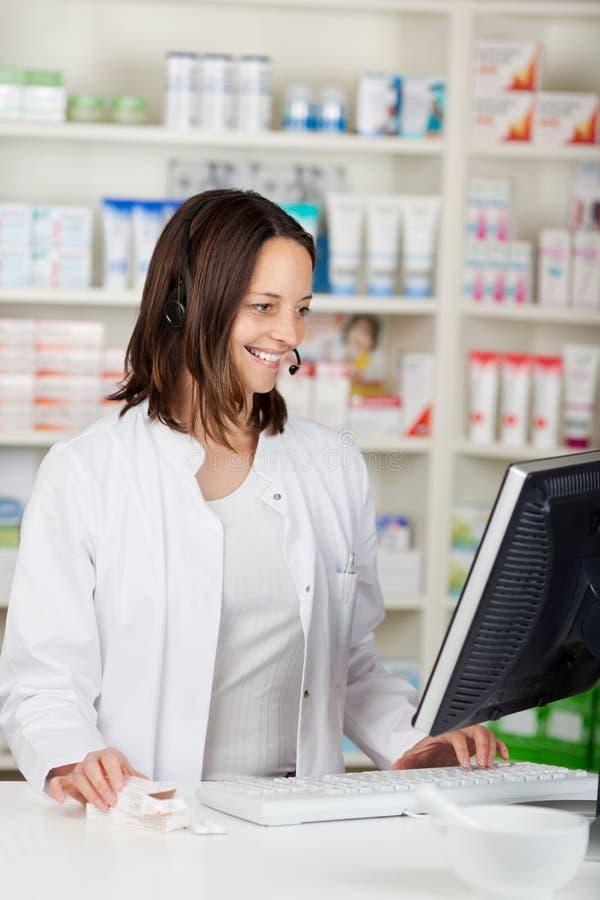 Femme d'affaires Conversing On Headset dans la pharmacie photos libres de droits