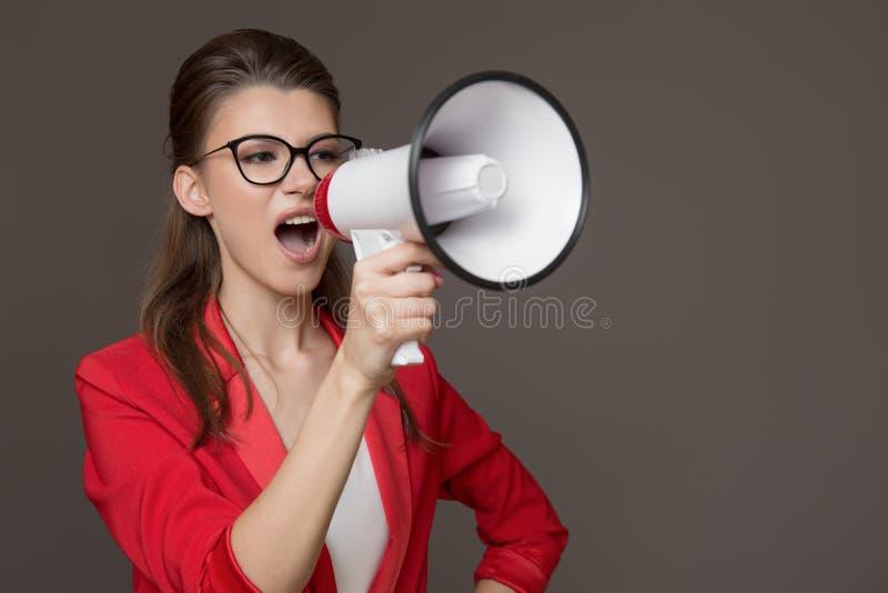 Femme d'affaires criant à un mégaphone Jeune jolie fille dans les verres et une veste rouge photos stock