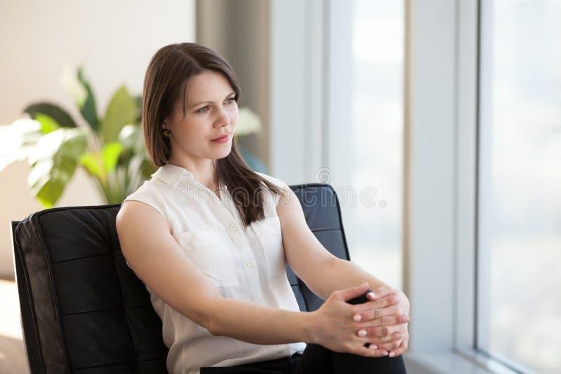 Femme d'affaires décontractée s'asseyant dans la chaise rêvant du nouveau travail images libres de droits