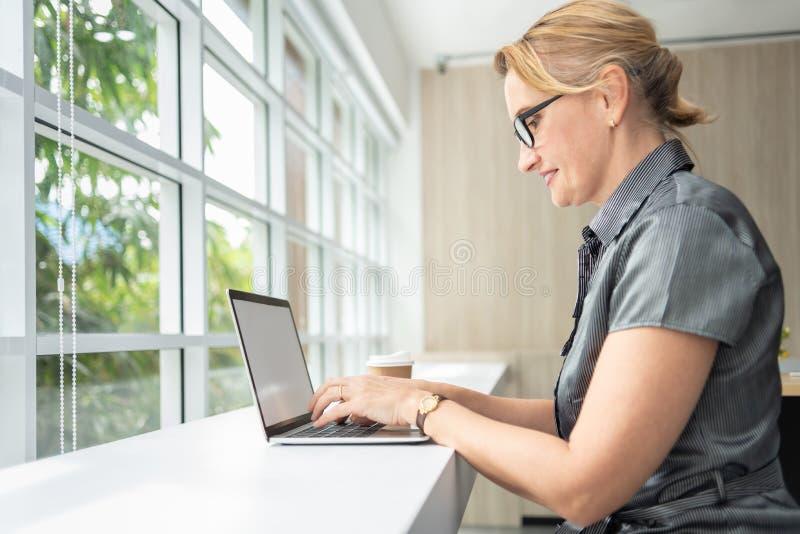 Femme d'affaires décontractée souriant et travaillant sur l'ordinateur portable photos stock