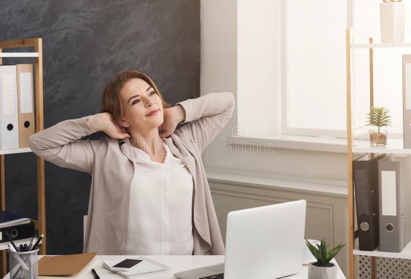 Femme d'affaires détendant sur le lieu de travail dans le bureau photographie stock
