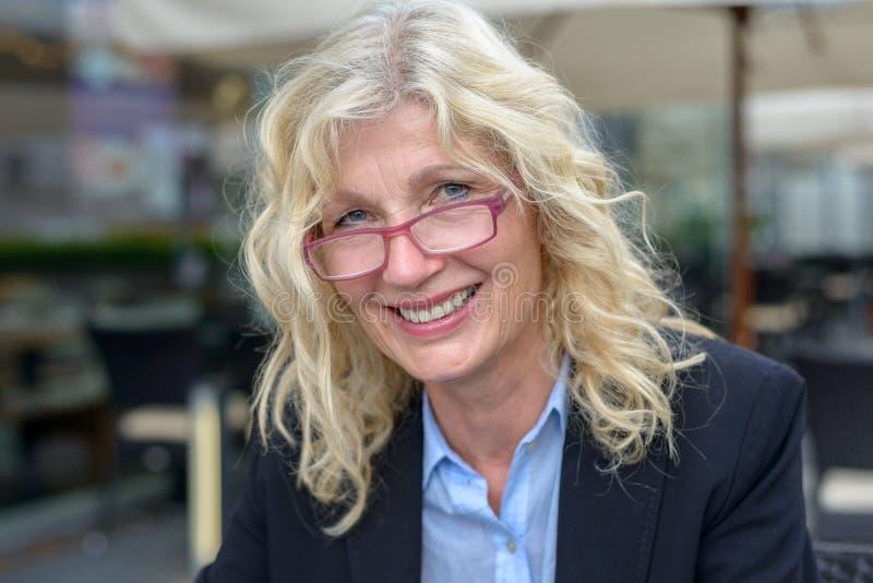Femme d'affaires d'une cinquantaine d'années souriant dans l'appareil-photo photos stock