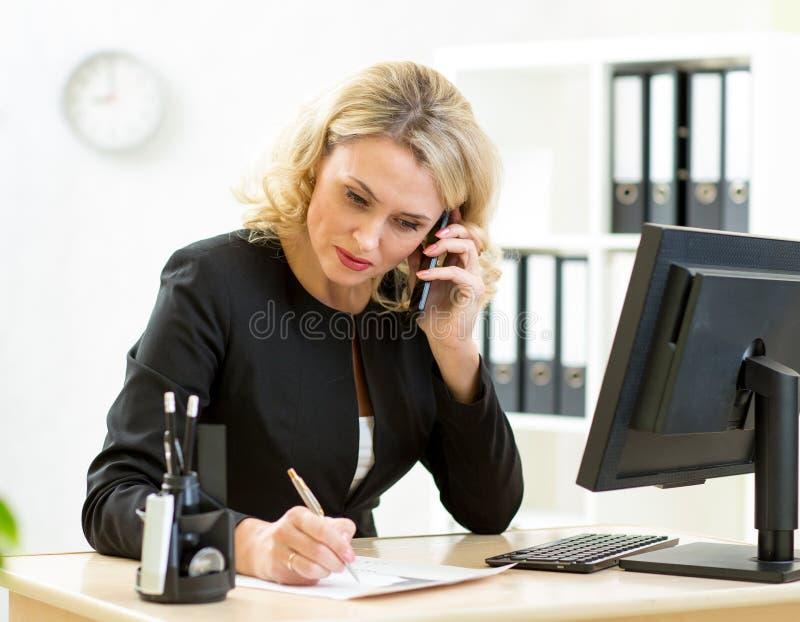 Femme d'affaires d'une cinquantaine d'années travaillant dans le bureau photos libres de droits