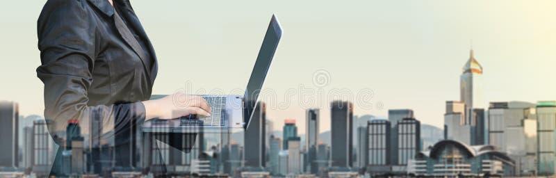 Femme d'affaires dactylographiant sur exposition d'ordinateur portable la double avec bleu photo stock