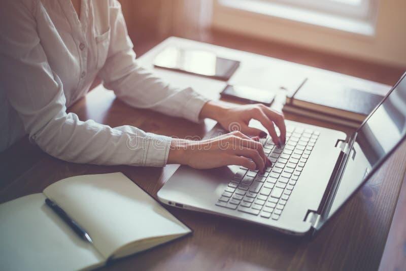 Femme d'affaires dactylographiant sur l'ordinateur portable à la femme de lieu de travail travaillant dans le clavier de main de  image stock
