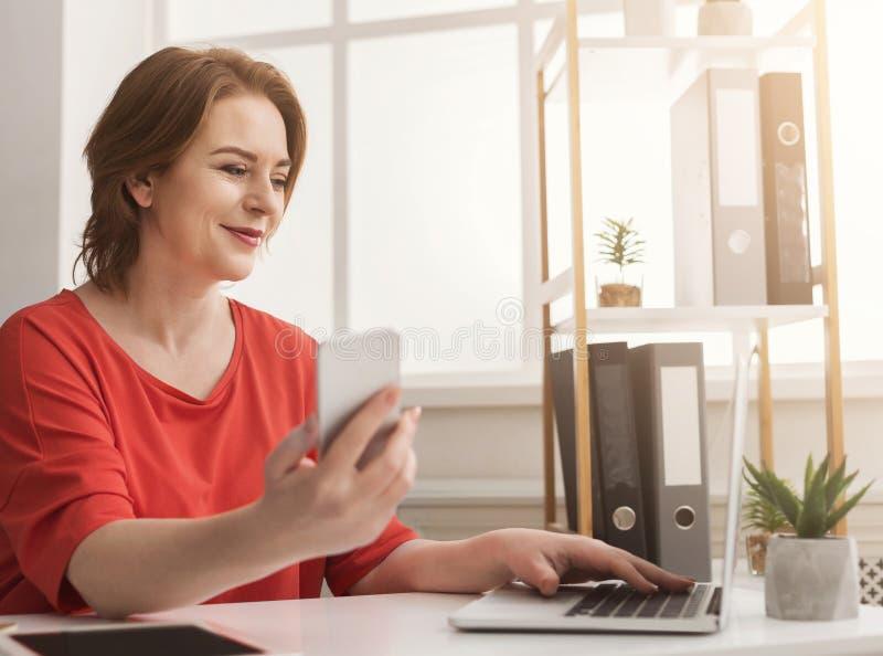 Femme d'affaires dactylographiant sur l'ordinateur portable et à l'aide du smartphone dans le bureau photo libre de droits