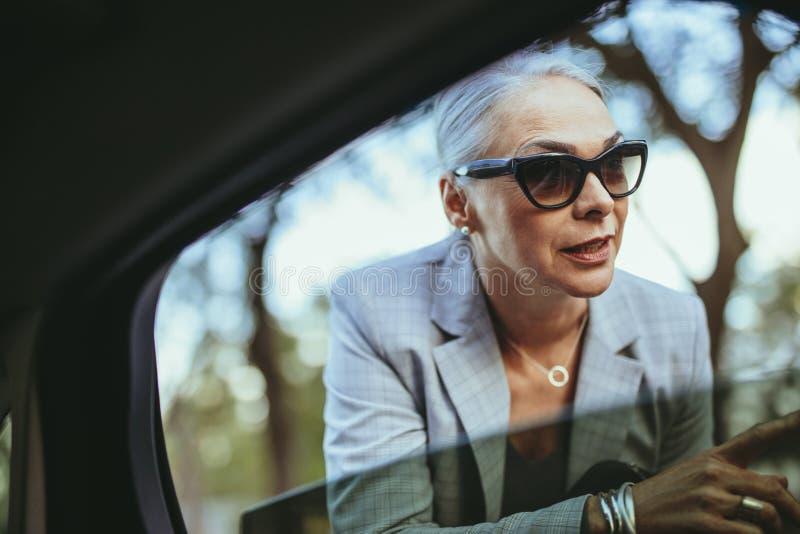 Femme d'affaires dans des lunettes de soleil parlant avec le chauffeur de taxi photographie stock libre de droits