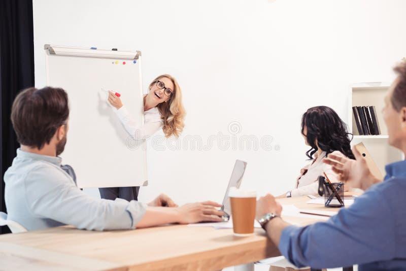 Femme d'affaires dans des lunettes se dirigeant au tableau blanc vide et regardant des associés au cours de la réunion image libre de droits
