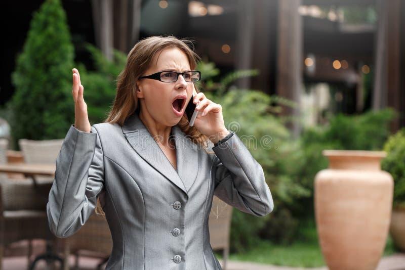 Femme d'affaires dans des lunettes se tenant sur la rue de ville ayant la conversation sur des mains de smartphone choquées photos stock
