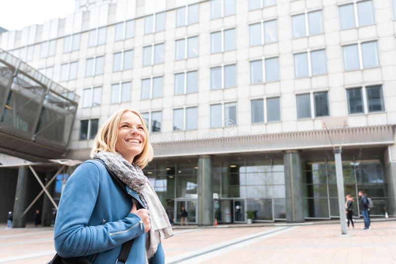 Femme d'affaires dans des vêtements sport descendant la rue devant un centre d'affaires images stock