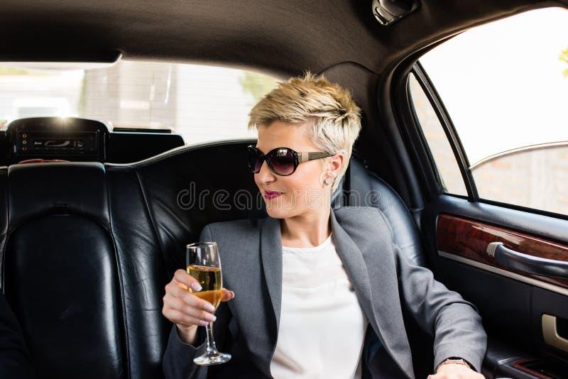 Femme d'affaires dans la limousine ayant le champagne image libre de droits