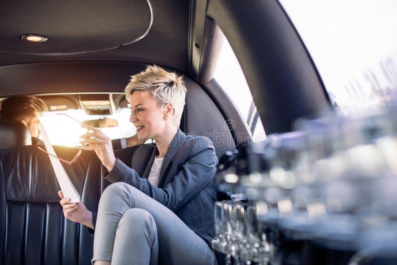 Femme d'affaires dans la limousine regardant des documents image libre de droits