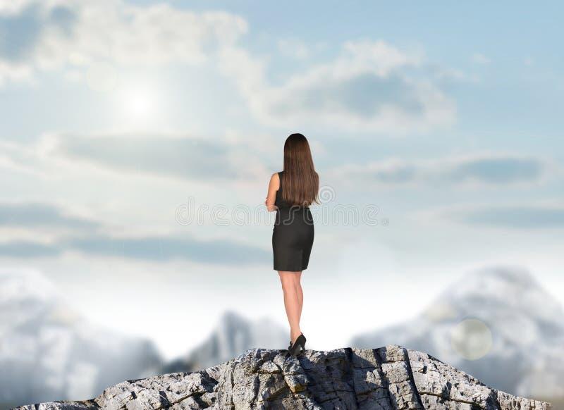 Femme d'affaires dans la robe sur le dessus de montagne photos stock