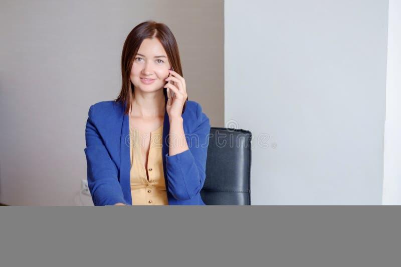 Femme d'affaires dans la tenue de détente prenant l'appel téléphonique de téléphone portable et écrivant des notes dans le calend images libres de droits