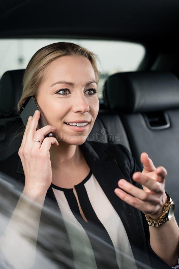 Femme d'affaires dans la voiture parlant sur le téléphone portable photographie stock libre de droits
