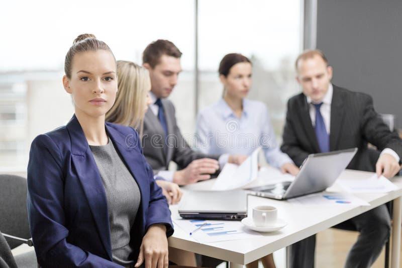 Femme d'affaires dans le bureau avec l'équipe sur le dos photographie stock libre de droits