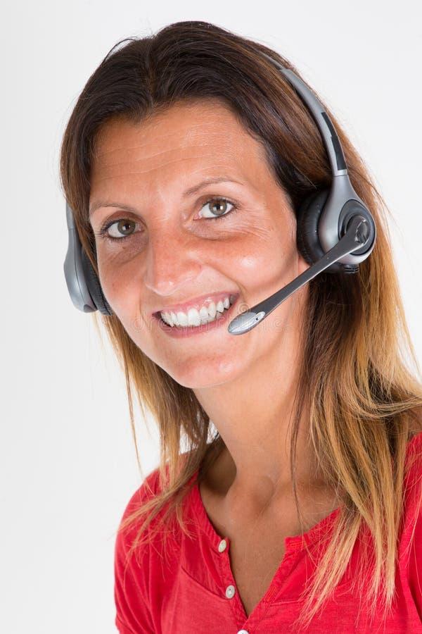 Femme d'affaires dans le bureau de callcenter avec le support à la clientèle d'aide de casque photo libre de droits