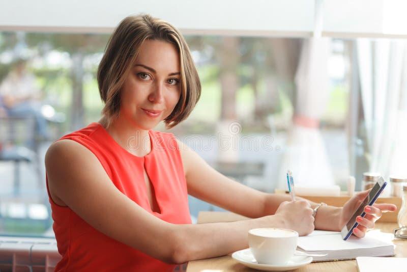 femme d'affaires dans le café dactylographiant par le téléphone portable photos stock